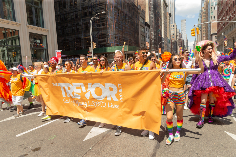 A photo of LGBTQ rights advocates holding a sign in support of the Trevor Project at the 2019 New York Pride March.
